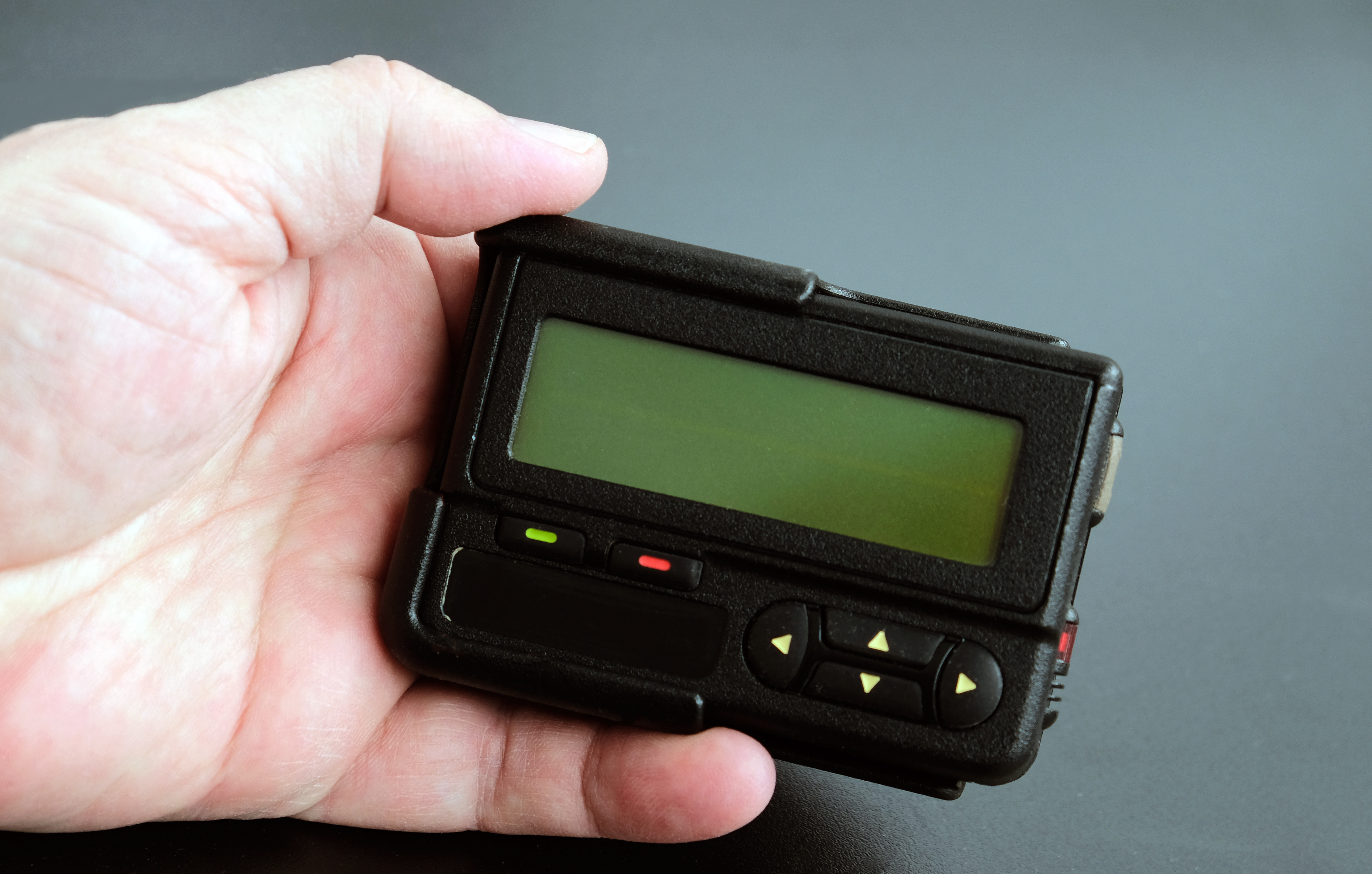Old black pager in hand